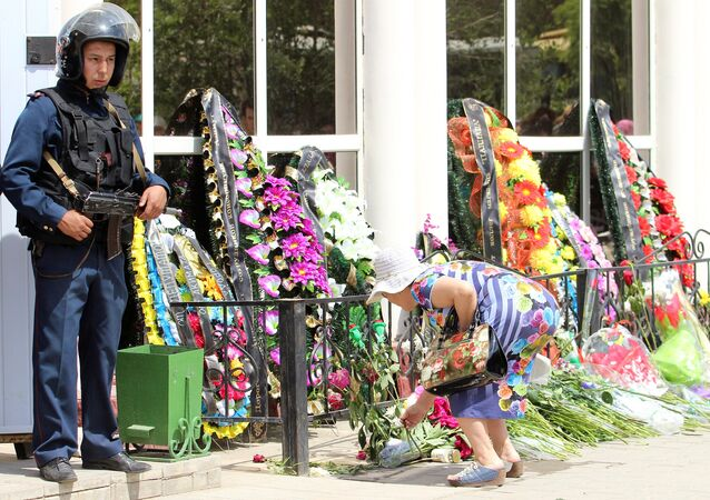 A woman places flowers outside the firearms shop, which was a target of a recent suspected Islamist militant attack, during the funeral of salesman Andrey Maksimenko in Aktobe, Kazakhstan, June 8, 2016