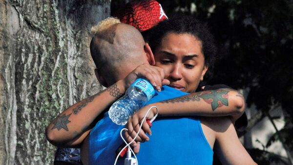Friends and family members embrace outside the Orlando Police Headquarters during the investigation of a shooting at the Pulse nightclub, where people were killed by a gunman, in Orlando, Florida, U.S June 12, 2016 - Sputnik International