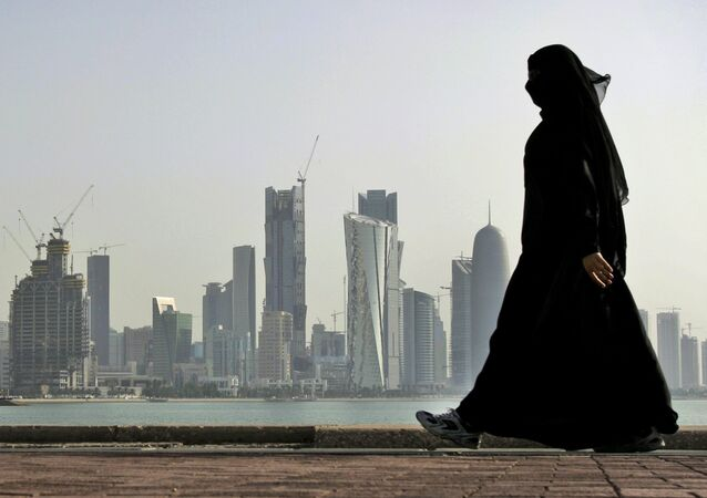 A Qatari woman walks in front of the city skyline in Doha, Qatar.