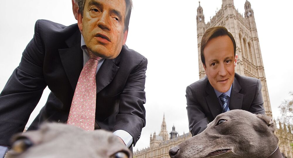 Men wear masks showing the faces of Gordon Brown (L) and David Cameron (R), as they pose with greyhounds during a photocall on April 26, 2010.