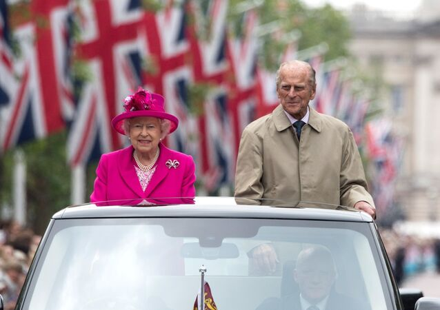 Britain's Queen Elizabeth II and Britain's Prince Philip, Duke of Edinburgh are driven along the Mall during the Patron's Lunch.