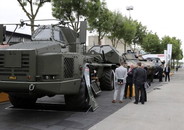 People look at military vehicles displayed on June 13, 2016 during the the Eurosatory defence and security international exhibition in Villepinte, near Paris.