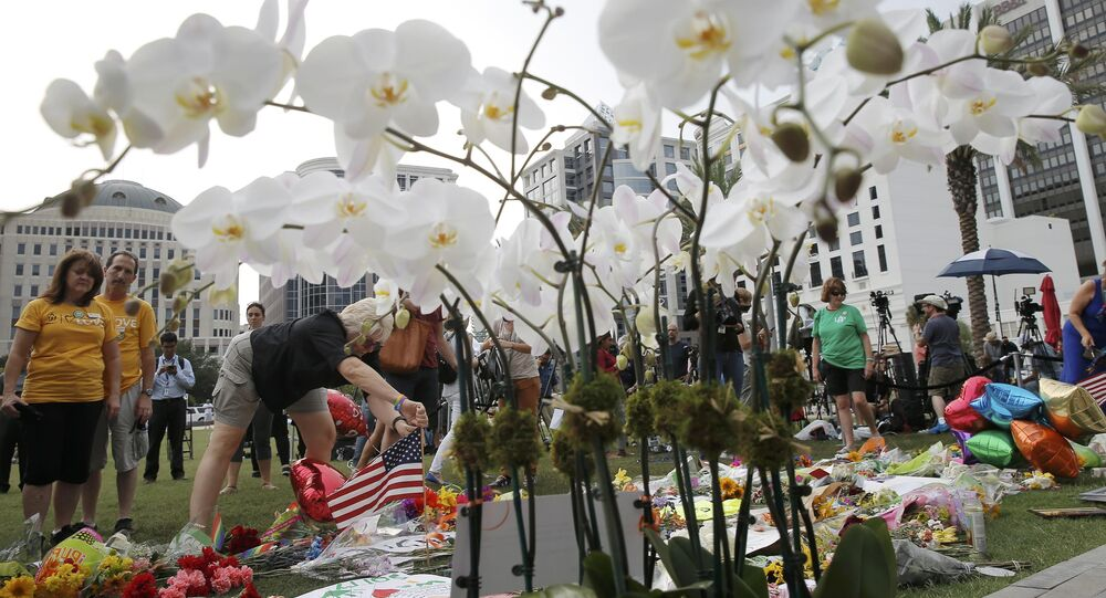 A visitor plants an American flag at a vigil for the shooting victims of Orlando's Pulse nightclub in Orlando, Florida, United States June 13, 2016