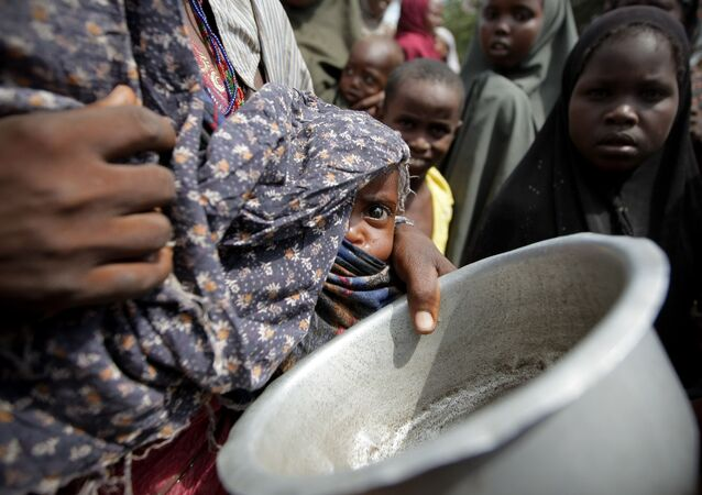 A woman holding her young malnourished baby queues for food at the Badbado camp for Internally Displaced Persons (IDPs).