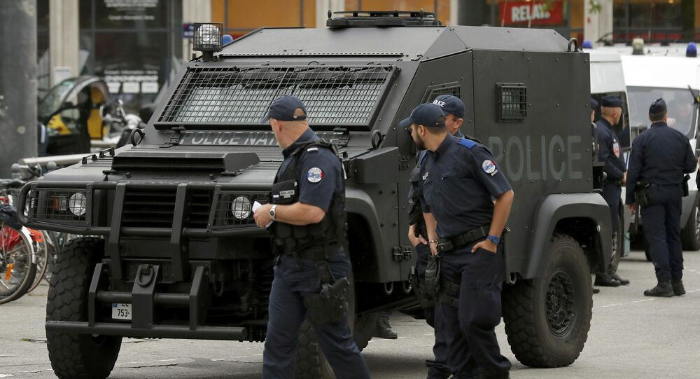 A polioce patrol looks at an armoured police vehicle parked in front of the train station in Lille, France.