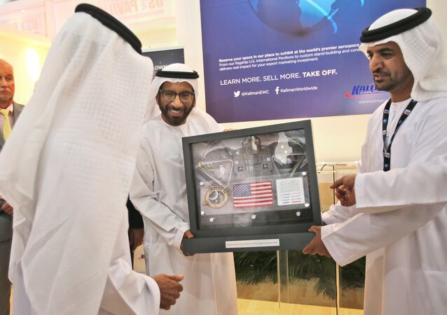 Khalifa Mohammed Al Rumaithi, Chairman of the UAE Space Agency, center, receives a United States of America flag and other memorabilia from the 1971 Apollo 14 lunar mission from Kallman Worldwide during the third day of the Dubai Airshow in the United Arab Emirates, Tuesday, Nov. 10, 2015.