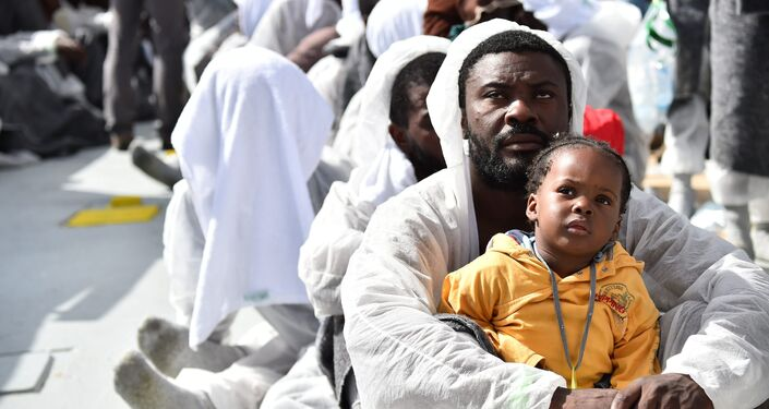 A man and his daughter wait during a distribution of meals aboard the rescue ship Aquarius, on May 25, 2016 a day after a rescue operation of migrants and refugees off the Libyan coast.