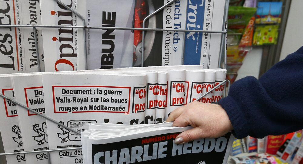 A woman picks up the issue of Charlie Hebdo.