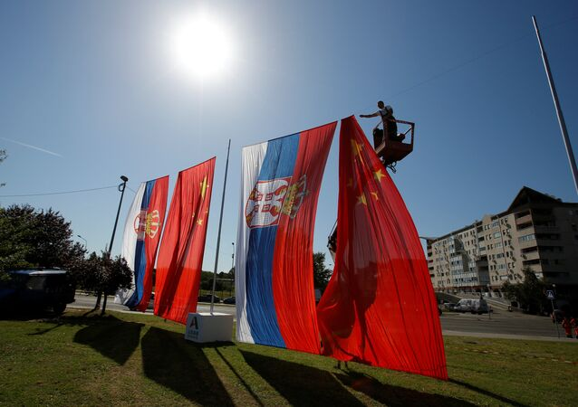 A worker adjusts Chinese and Serbian flags for the upcoming visit of Chinese President Xi Jinping