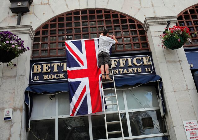 A worker places the Union Jack flag on the facade of a shop at Casesmates square where British Prime Minister David Cameron will attend a 'Stronger In' campaign event in the British overseas territory Gibraltar, historically claimed by Spain, June 16, 2016.