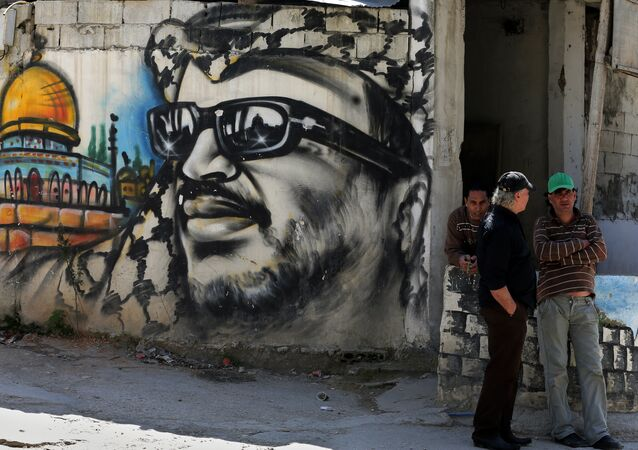 Palestinian refugees stand next to graffiti bearing a portrait of late Palestinian President Yasser Arafat at the Ain Al-Helweh refugee camp, near the southern Lebanese city of Sidon, on March 16, 2015
