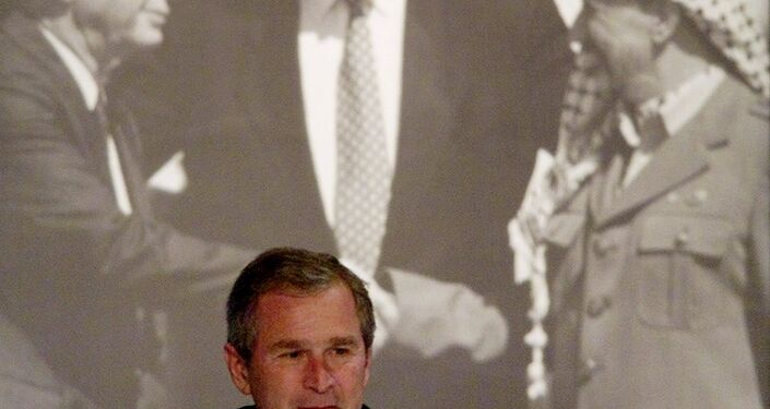George W. Bush sits in front photo of former Israeli Prime Minister Yitzhak Rabin and PLO Chairman Yasser Arafat.
