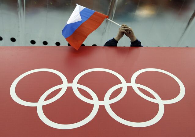 In this Feb. 18, 2014 file photo, a Russian skating fan holds the country's national flag over the Olympic rings before the start of the men's 10,000-meter speedskating race at Adler Arena Skating Center during the 2014 Winter Olympics in Sochi, Russia