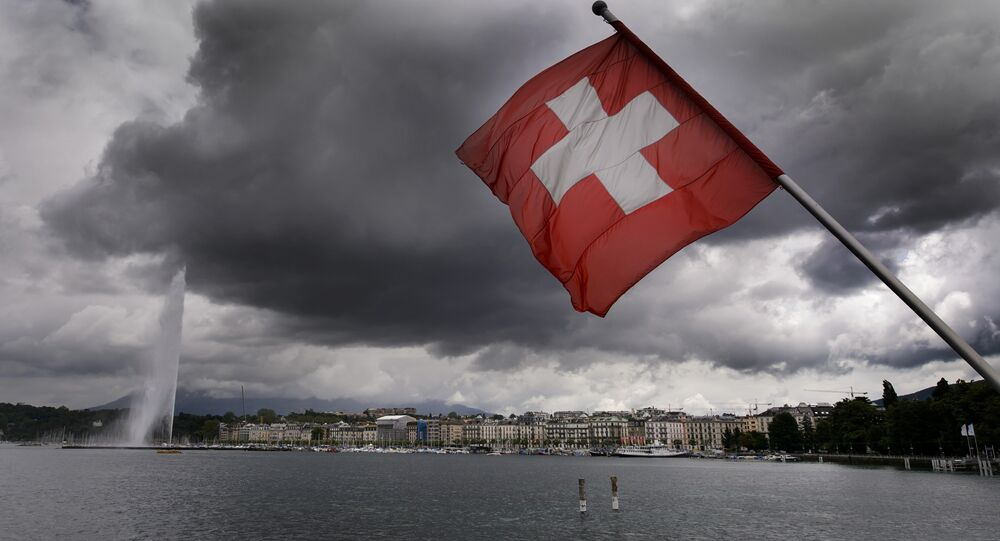 A Swiss flag flies on the shores of Geneva Lake in front of the Geneva Fountain (L) on June 14, 2013 in the center of Geneva
