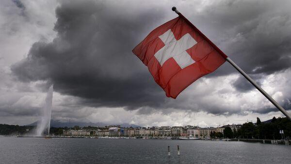 A Swiss flag flies on the shores of Geneva Lake in front of the Geneva Fountain (L) on June 14, 2013 in the center of Geneva - Sputnik International