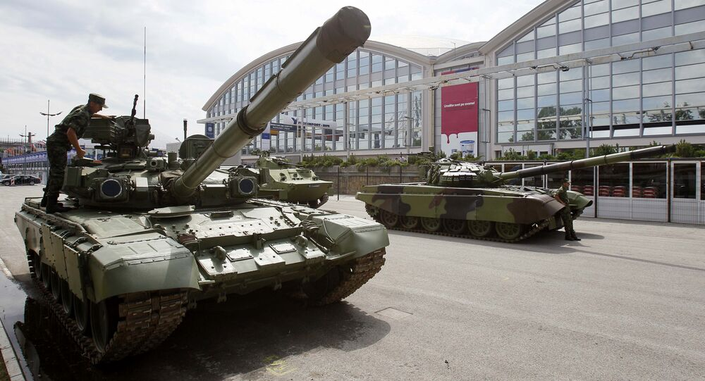A Serbian army soldier inspects an M-84 battle tank during a defense fair, in Belgrade, Serbia, Tuesday, June 28, 2011