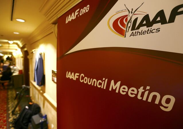 Journalists are seen near a logo of the International Association of Athletics Federations (IAAF) at a hotel where the IAAF council holds a meeting in Vienna, Austria, June 17, 2016