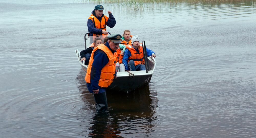 Emergency services bring children to shore after the Karelia boat disaster