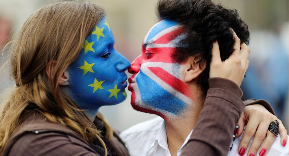 Two activists with the EU flag and Union Jack painted on their faces kiss each other in front of Brandenburg Gate to protest against the British exit from the European Union, in Berlin, Germany, June 19, 2016.