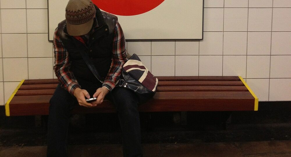 Commuter using a cellphone on the London Underground