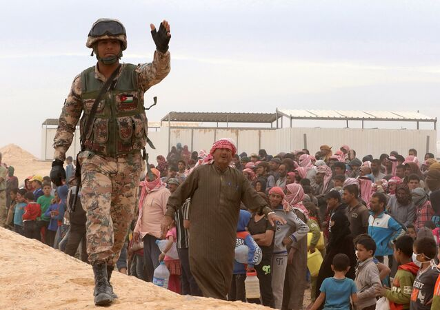 A Jordanian soldier stands guard as Syrian refugees (file)