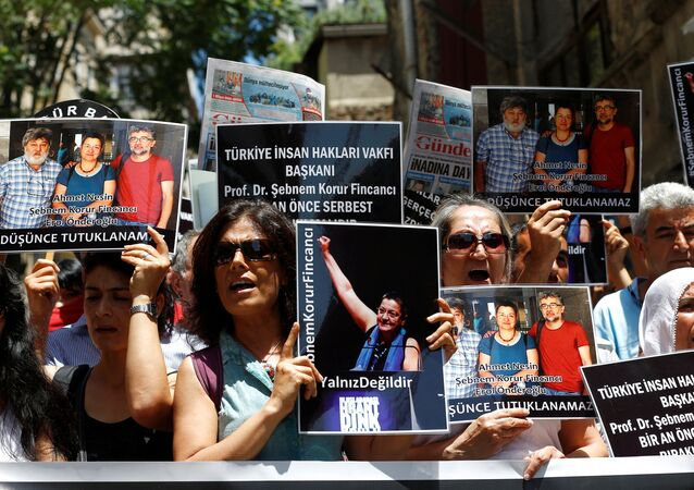 Demonstrators shout slogans as they hold pictures of Ahmet Nesin, Sebnem Korur Fincanci and Erol Onderoglu during a protest against arrest of the three prominent campaigners for press freedom, in front of the pro-Kurdish Ozgur Gundem newspaper in central Istanbul, Turkey, June 21, 2016.
