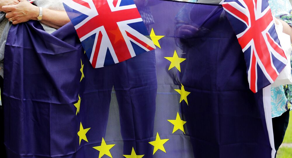 People hold Union Flags and the EU flag at a kiss chain event organised by pro-Europe 'remain' campaigners seeking to avoid a Brexit. file photo