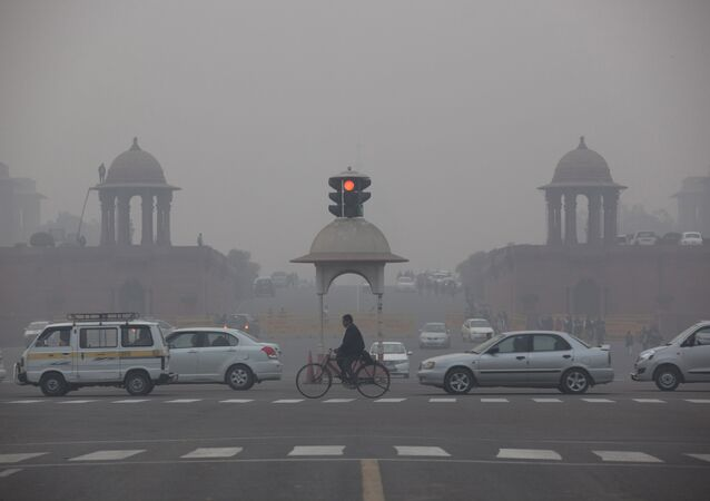 Vehicles move past the Presidential Palace as smog engulfs the evening in New Delhi, India.