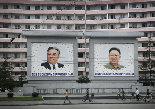 North Koreans are dwarfed against giant portraits of the late North Korean leaders Kim Il Sung and Kim Jong Il as they walk past an apartment building on Wednesday, June 22, 2016, in Wonsan, North Korea.