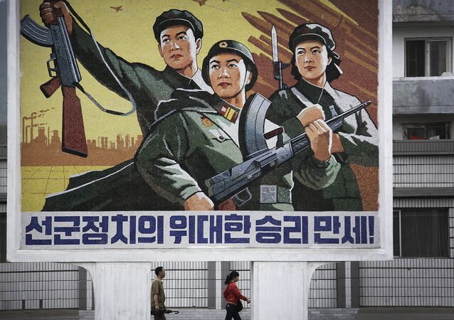 A North Korean man and woman walk under a mural with a message which reads Long live the great victory of the army-first policy in the city center of Wonsan on Wednesday, June 22, 2016, in Wonsan, North Korea.