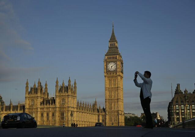 A man takes a photo as he stands on Westminster bridge with the Houses of Parliament in the background in London, Friday, June 24, 2016.