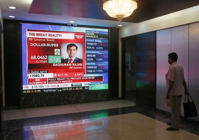 A man watches Reserve Bank of India governor Raghuram Rajan commenting on the situation after stock markets tumbled worldwide, on a stock markets indicator board in Mumbai, India, Friday, June 24, 2016.