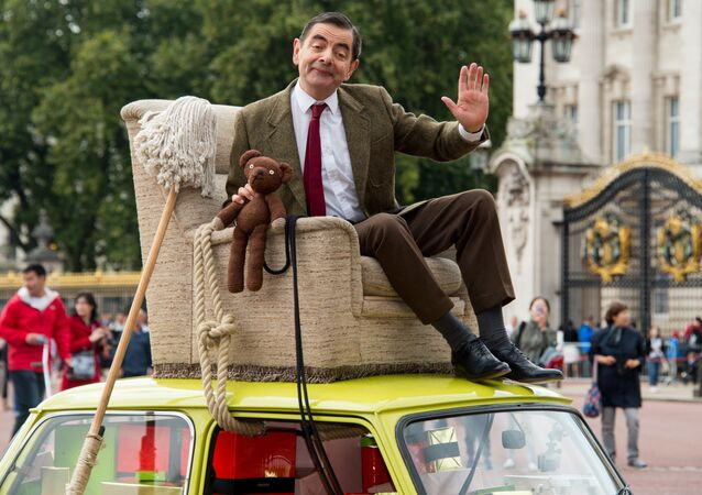 British actor Rowan Atkinson, dressed as Mr Bean, sits on top of a Mini Cooper outside Buckingham Palace, London, to promote the 25th anniversary of Mr Bean, London, Friday, Sept. 4, 2015.