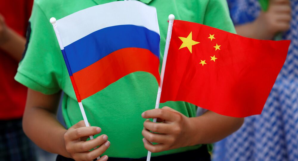 A child holds the national flags of Russia and China prior to a welcoming ceremony for Russian President Vladimir Putin outside the Great Hall of the People in Beijing, China, June 25, 2016