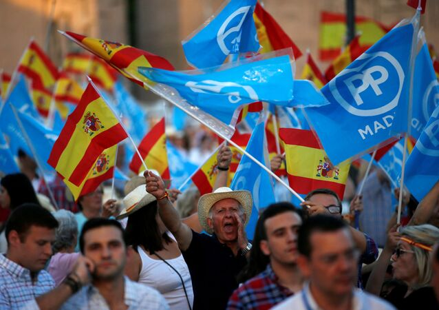 Popular Party supporters hold Spanish flags as they wait for the arrival of Spain's acting Prime Minister and People's Party (PP) leader Mariano Rajoy before the final campaign rally for Spain's general election in Madrid, Spain, June 24, 2016