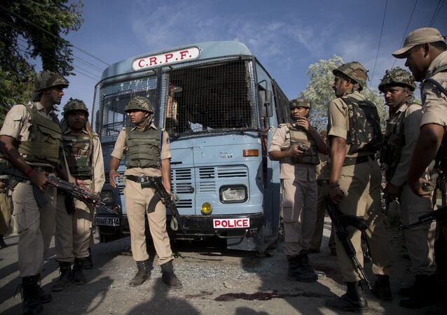 Indian security personnel stand guard near the bus that was carrying paramilitary soldiers damaged after a highway ambush by suspected rebels in Pampore, on the outskirts of Srinagar, Indian controlled Kashmir, Saturday, June 25, 2016