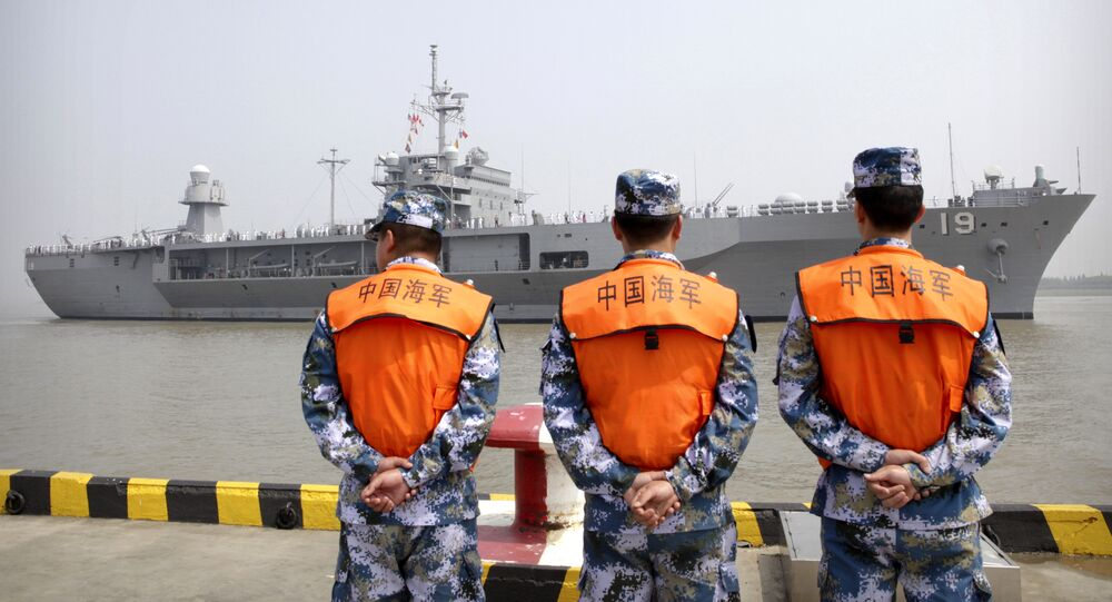 Soldiers from the Chinese People's Liberation Army (PLA) Navy watch as the USS Blue Ridge arrives at a port in Shanghai, Friday, May 6, 2016