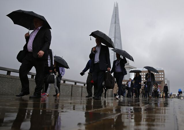 Commuters heading into the City of London walk in the rain across London Bridge, in front of the Shard skyscraper, in central London on June 27, 2016.