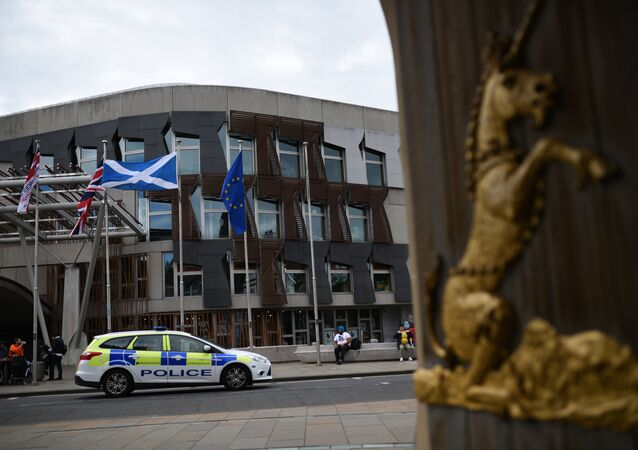 The Union flag, (2L), the Scottish Saltire flag (2R) and the European Union (EU) flag (R) fly outside the Scottish Parliament building in Edinburgh, Scotland on June 25, 2016, following the pro-Brexit result of the UK's EU referendum vote