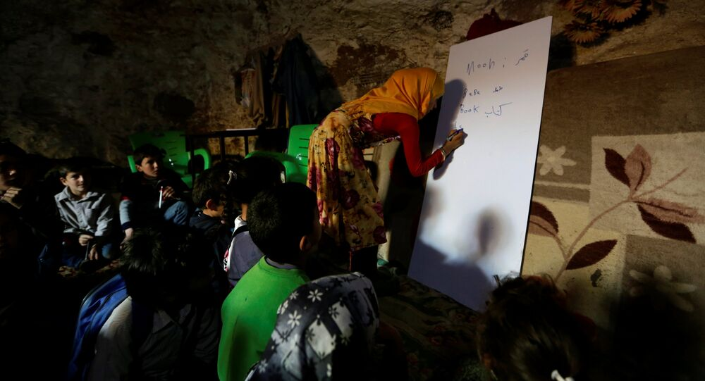 A teacher conducts a lesson for internally displaced children inside a cave in the rebel-controlled village of Tramla, in Idlib province, Syria March 27, 2016