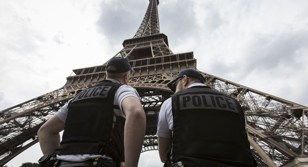 French riot police officers patrol under the Eiffel Tower, near the entrance of the soccer fan zone, prior to the Euro 2016 Group A soccer match between France and Romania, in Paris, Friday, June 10, 2016