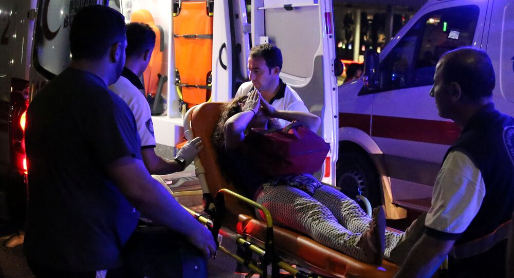 An injured woman covers her face as she is carried by paramedics into ambulance at Istanbul Ataturk airport, Turkey, following a blast June 28, 2016.