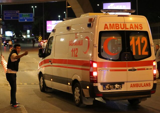 A policeman gestures in front of an ambulance at Istanbul Ataturk airport, Turkey, following a blast June 28, 2016.