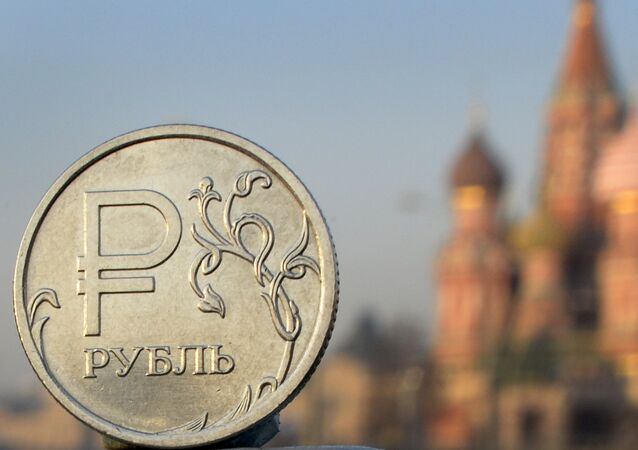 A Russian ruble coin is pictured in front of St. Basil cathedral in central Moscow