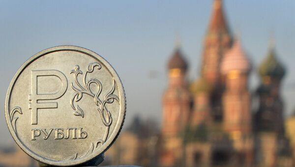 A Russian ruble coin is pictured in front of St. Basil cathedral in central Moscow - Sputnik International