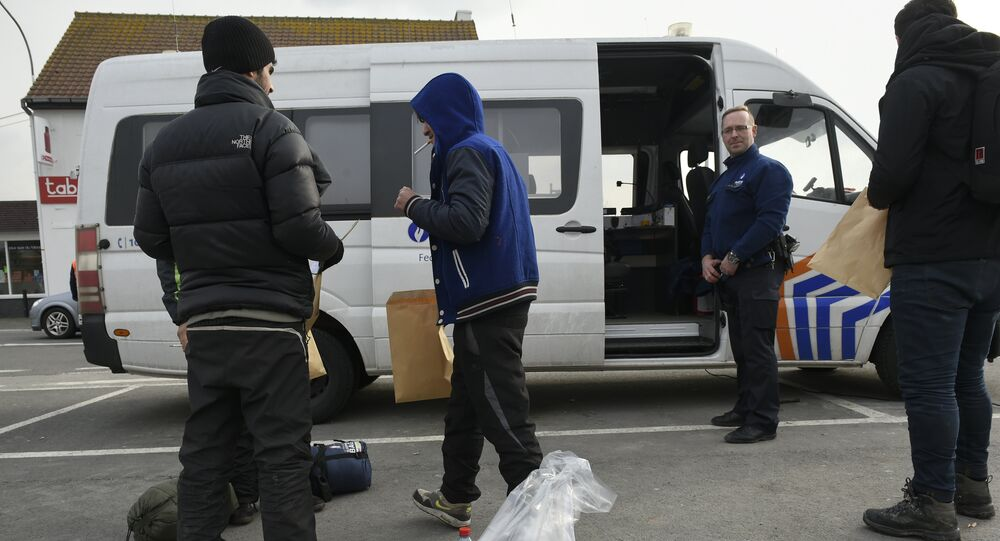 Migrants, who were arrested earlier in Belgium, are released by Belgian police officers near the Belgian-French border on February 26, 2016 in Adinkerke.