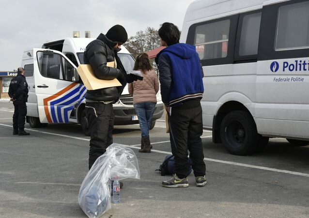 Migrants, who were arrested earlier in Belgium, are released by Belgian police officers near the Belgian-French border in Adinkerke.