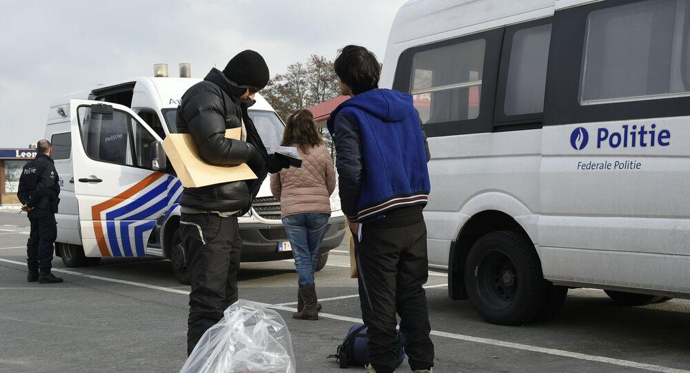 Migrants and  Belgian police officers near the Belgian-French border in Adinkerke.