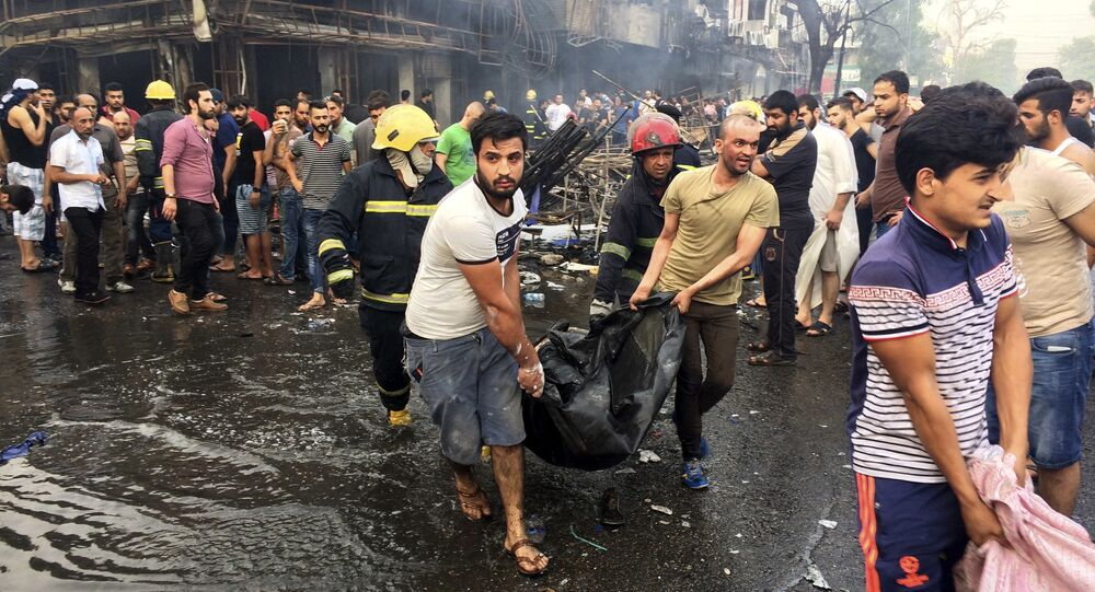 Iraqi firefighters and civilians carry bodies of victims killed in a car bomb at a commercial area in Karada neighborhood, Baghdad, Iraq, Sunday, July 3, 2016