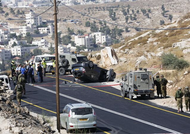 Israeli soldiers secure the scene of a shooting attack near Hebron, West Bank, Friday, July 1, 2016